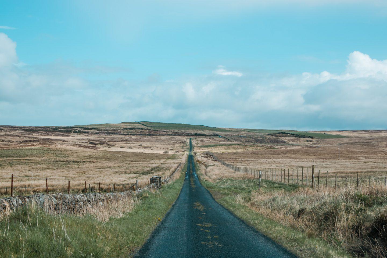 Mittendurch die Landschaft führt eine lange, schnurgerade, schmale Straße