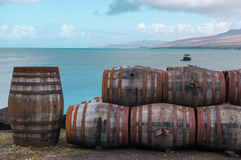 Fässer bei Bunnahabhain Whisky Destillery - eine wunderschöne Stimmung am blauen Meer in Islay, Schottland