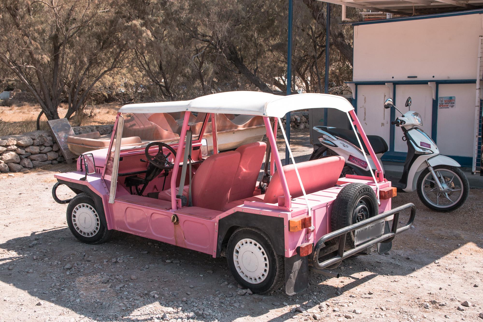 Rosaroter Mini Moke, ein älteres Auto das aussieht wie ein niedriggelegter Jeep, entdeckt beim Inselhüpfen auf Patmos