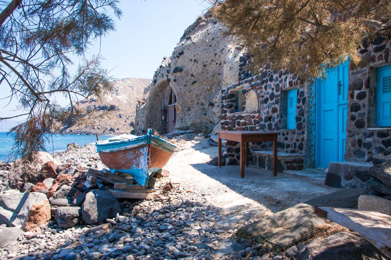 Thirassia - Bootsgaragen im Hafen Riva - altes Holzboot, Tisch und Türen im Felsen kombinieren sich zu einem perfekten Stilleben